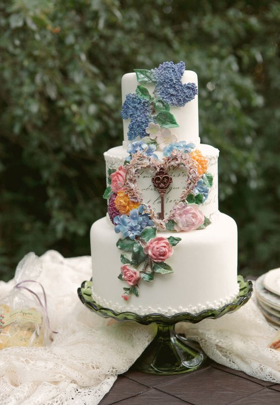 an enchanting secret garden wedding cake in white decorated with pastel blooms and foliage of sugar is wow
