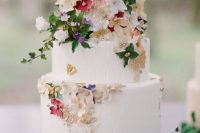 32 a white buttercream wedding cake decorated with gold foil, sugar flowers and real leaves, beads and butterflies is amazing