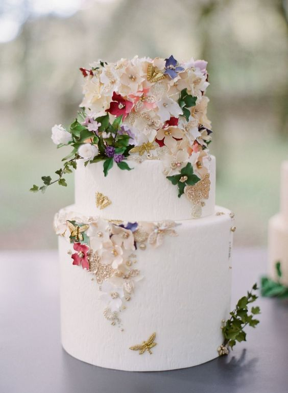 a white buttercream wedding cake decorated with gold foil, sugar flowers and real leaves, beads and butterflies is amazing