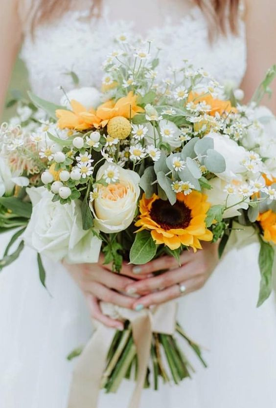 a lovely summer wedding bouquet with daisies, sunflowers, greenery, white blooms and berries is a chic idea