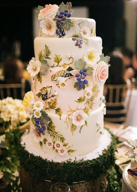 a whimsical secret garden wedding cake in white, with fresh and sugar blooms, grapes and leaves is amazing
