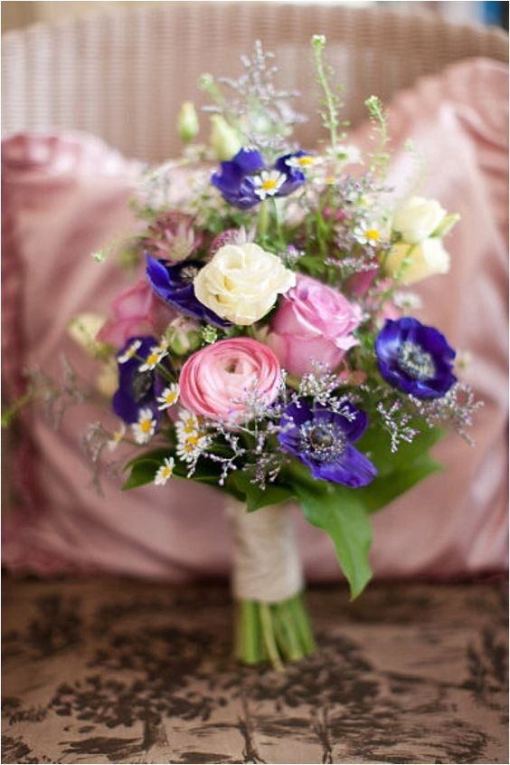 a lovely wedding bouquet of daisies as fillers, pink ranunculus and roses, purple anemones, greenery is a simple and cool idea