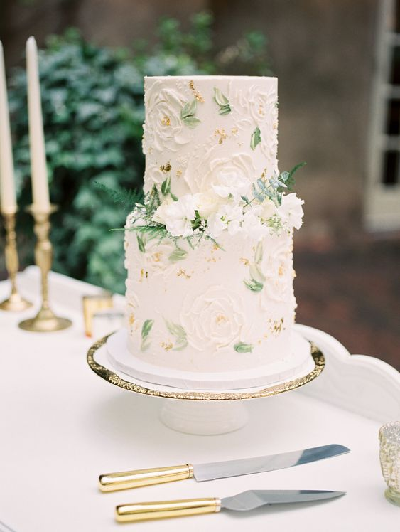 a sophisticated secret garden wedding cake in neutrals with sugar blooms and painted leaves, with fresh white flowers and ferns is amazing