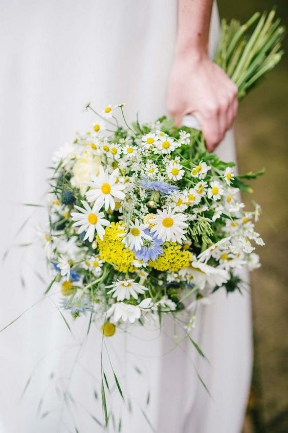 a lovely wedding bouquet with daisies, blue and mustard blooms and greenery is a simple and pretty idea for a rustic wedding
