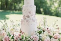 37 a delicate secret garden wedding cake with pink and mauve blooms painted and lush blooms around is amazing
