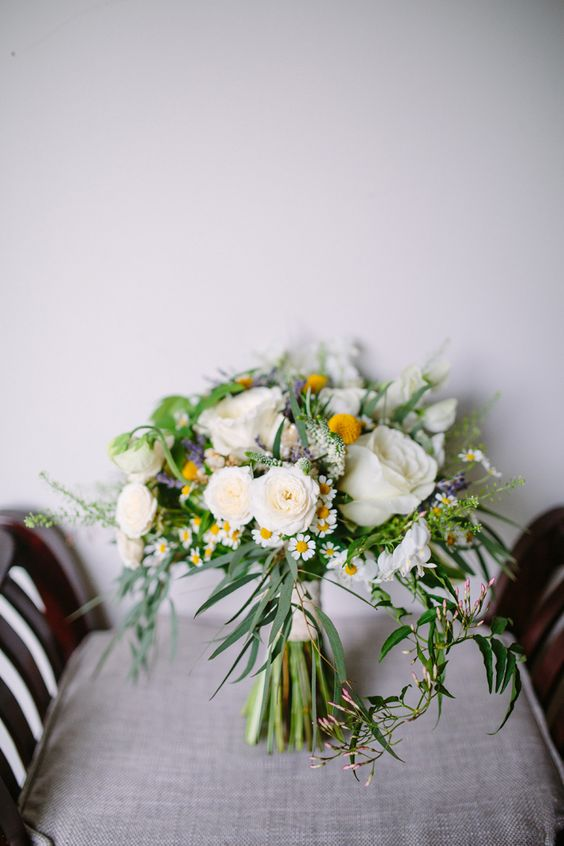 a summer wedding bouquet of daisies, white roses and ranunculus, grasses and billy balls is a beautiful option for spring or summer