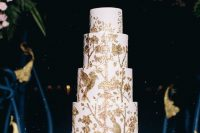 38 a white wedding cake with gold painted birds, branches and leaves is a very refined and bold idea for a secret garden wedding