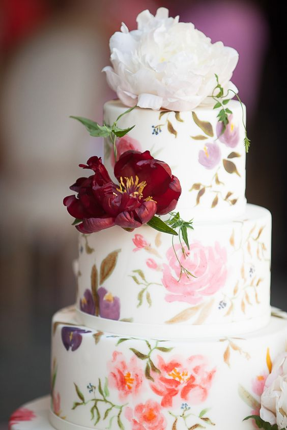a beautiful secret garden wedding cake with painted pastel blooms and leaves and some bold fresh flowers is wow