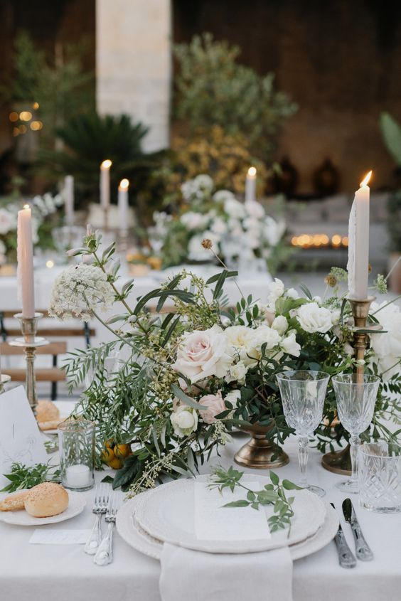 a beautiful and chic wedding centerpiece of white and blush blooms and greenery plus white and blush candles around