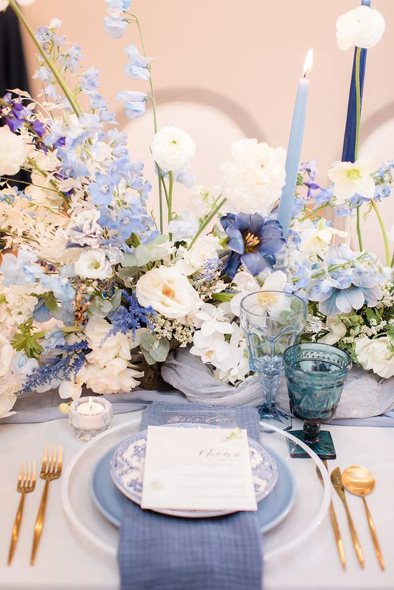 a beautiful and inspiring secret garden wedding centerpiece with lilac, blue and white blooms and blue candles is amazing