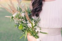 a beautiful and textural long stem wedding bouquet with white blooms, green ones, greenery, dried grasses and white ribbons