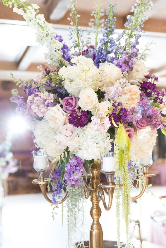 a beautiful and unusual secret garden wedding centerpiece of candles, white, purple and lilac blooms and greenery