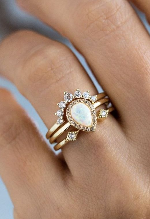 a beautiful and vintage-inspired yellow gold stacked wedding ring with a pear-shaped opal and an arched diamond ring