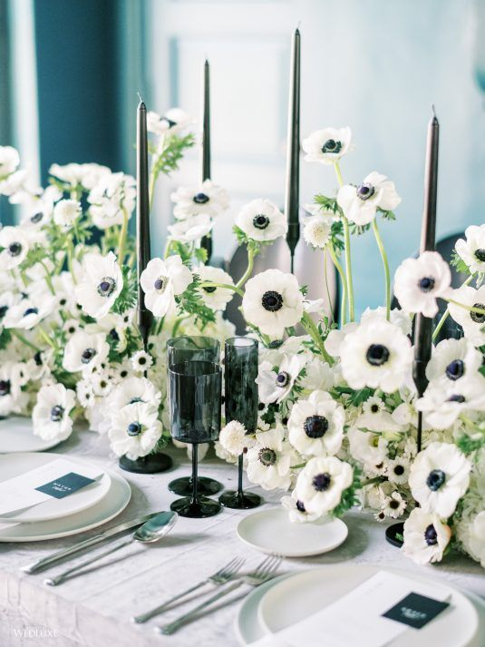 a beautiful anemon wedding centerpiece with elegant black candles and black glasses is lovely for a contemporary refined tablescape