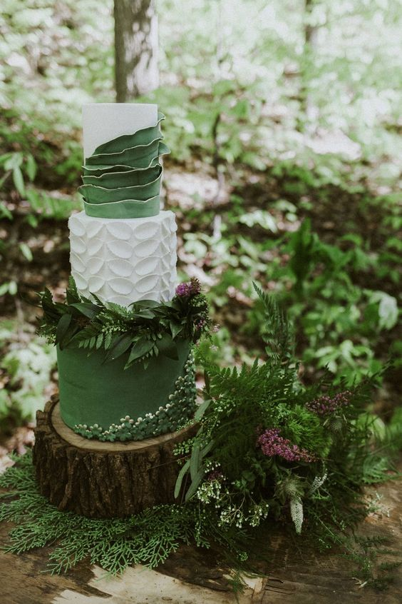 a beautiful enchanted forest wedding cake with a green and a white petal tier, with a white and green ruffles, with greenery decor