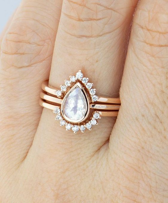 a beautiful rose gold stacked wedding ring with a drop-shaped central one and arched diamond rings to frame it is chic