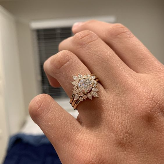 a beautiful stacked engagement ring with a central large diamond one and two arched diamond rings to frame it