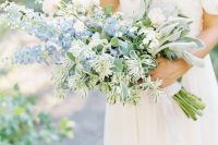 a beautiful wedding bouquet including white roses and blue delphinium and various types of greenery for a French country wedding