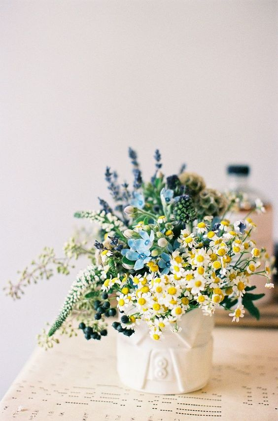 a beautiful wedding centerpiece that includes daisies, privet berries, astilbe, lavender and some more blooms is chic