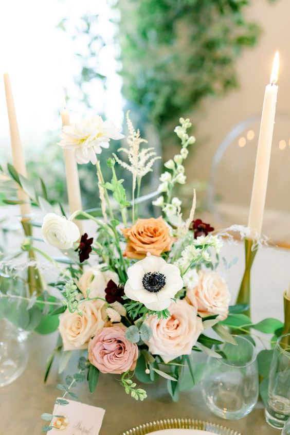 a beautiful wedding centerpiece with blush and rust roses, white ranunculus and anemones, greenery and elegant tall candles