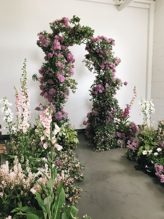 a beautiful wedding ceremony space with an arch made of greenery and lilac, with greenery and blooms around feels like a real indoor garden