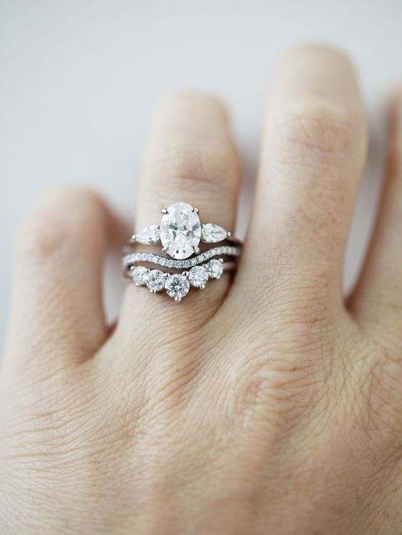 a beautiful white diamond wedding ring stack with an upper oval shaped one, a wavy diamond ring and a lower larger diamond ring