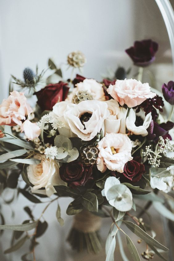a bold and cool wedding bouquet of burgundy and white roses, blush ones, white anemones, seed pods and thistles, greenery for the fall