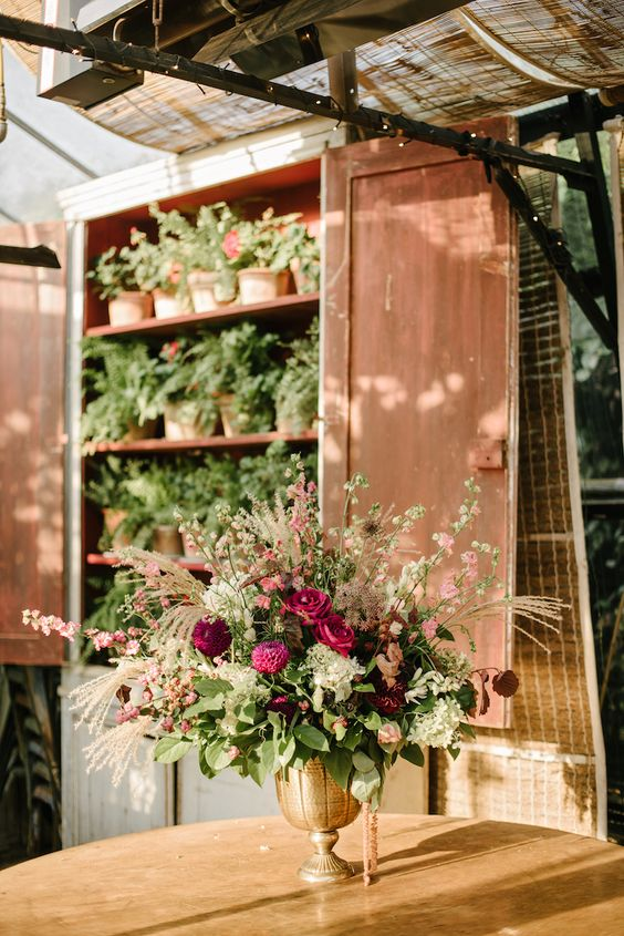 a bold secret garden wedding of a gilded vase, dark blooms and blush ones and some greenery is a chic idea for the fall