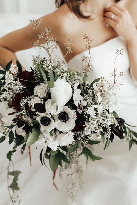 a bold wedding bouquet of white anemones and ranunculus, greenery and blooming branches is a stylish idea for a bride who loves contrasts