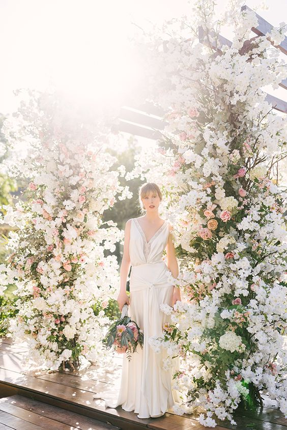 a breathtaking wedding altar with greenery, blush, peachy and white blooms is a very refined and bold idea that will take everyone's breath away