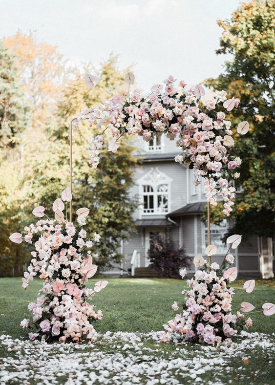 a breathtaking wedding arch covered with pink and blush blooms not entirely but partly, lots of petals on the ground for a romantic ceremony space