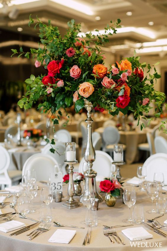 a bright floral wedding centerpiece with much greenery and bold blooms looks magical and fantastic, like in a fairy-tale