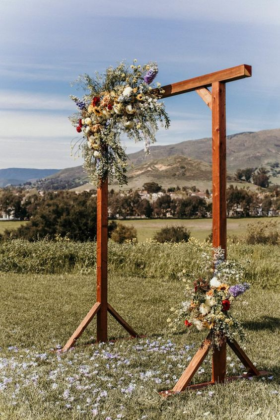 a bright rustic wedding arch of wooden slabs, greenery and colorful blooms is a lovely idea for both an indoor and outdoor wedding