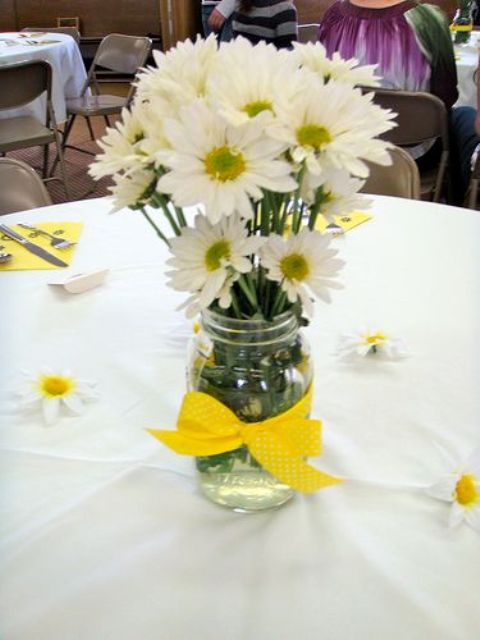 a bright rustic wedding centerpiece of daisies and a yellow bow on the jar is a veyr cute and fun idea