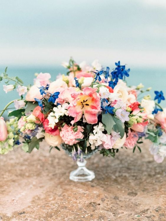 a bright secret garden wedding centerpiece of a glass bowl, bold pink and blue blooms and some foliage is chic and amazing