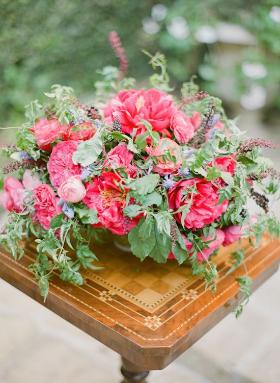 a bright statement secret garden wedding centerpiece of hot pink peonies, pink ranunculus and greenery plus some thistles