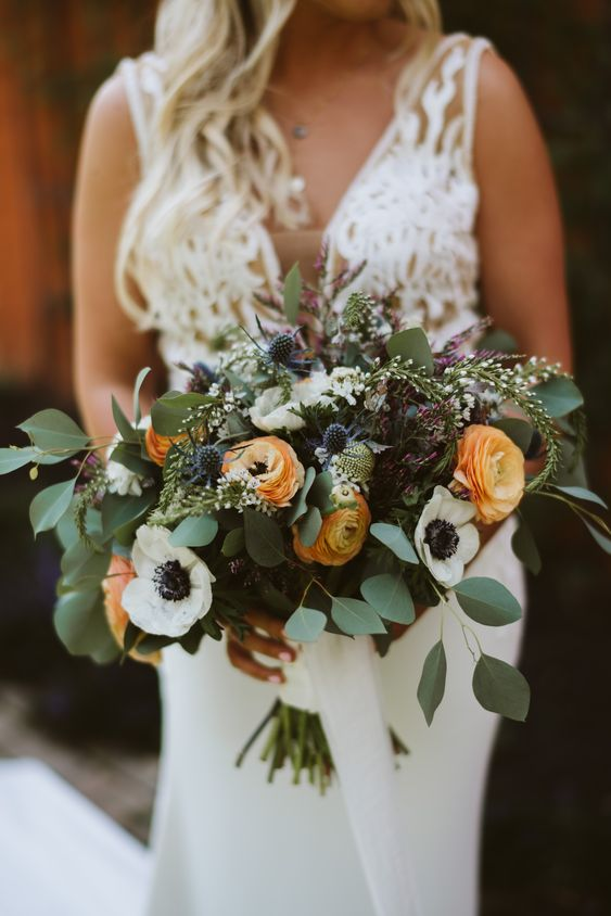 a bright wedding bouquet of yellow ranunculus, white anemones, thistles, eucalyptus is great for summer or fall
