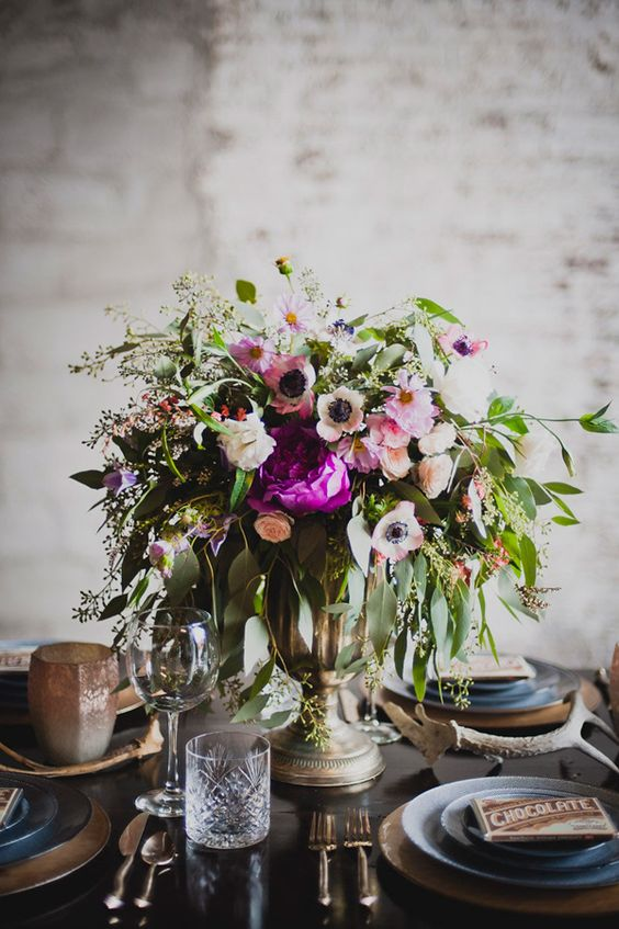 a bright wedding centerpiece of hot pink and white anemones, various types of greenery and a beautiful brass vase is wow