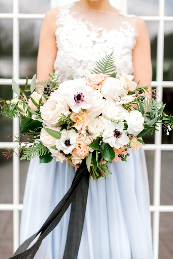 a catchy wedding bouquet of white anemones, peachy and blush roses and peonies, fern and berries and some eucalyptus is wow