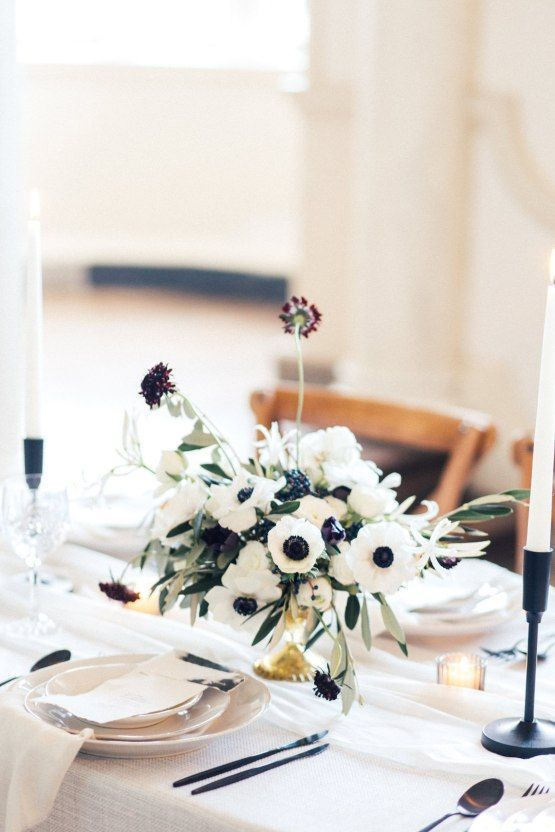 a catchy wedding centerpiece of white anemones and dark purple blooms plus some greenery and candles around is amazing