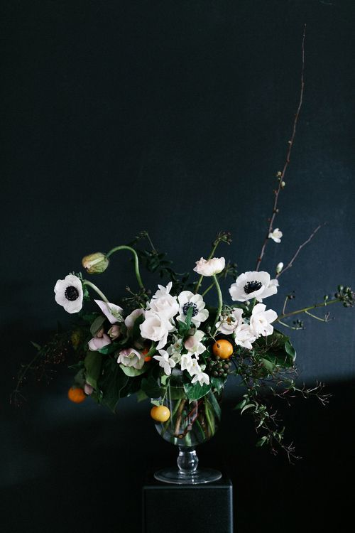 a catchy wedding centerpiece of white anemones and other blooms, greenery, twigs and branches, with some citrus in a clear vase
