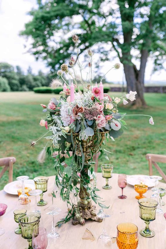 a chic and bright secret garden wedding centerpiece of a tall vase, pink blooms, greenery and seed pods looks very quirky