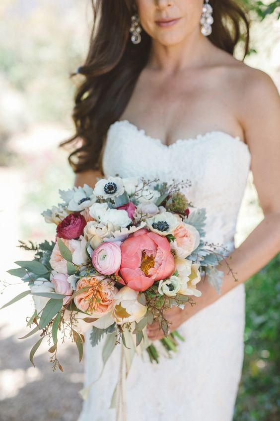 a chic and bright summer wedding bouquet of pink and blush peonies, white anemones, peony roses, pale and usual greenery and twigs