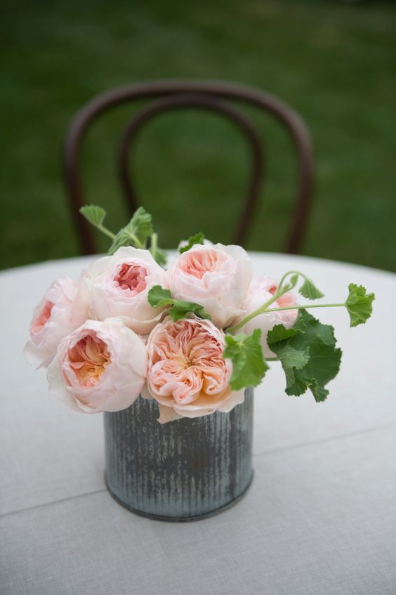 a chic and easy wedding centerpiece of blush peonies and greenery in a metal vase is a stylish solution for summer