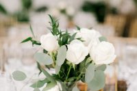 a chic and simple wedding centerpiece of a vase, white roses and greenery, pebbles and a faceted candleholder