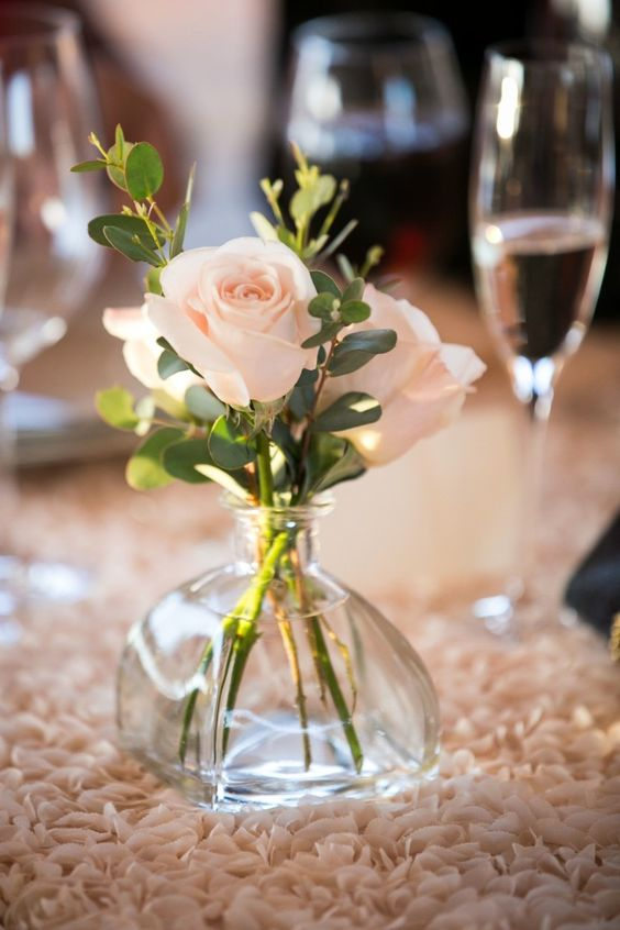 a chic and simple wedding centerpiece of a vase with blush roses and eucalyptus is a stylish and cool idea for a wedding