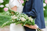 a chic and stylish bridal look with a ilk wedding dress and a dreamy long stem white and blush wedding bouquet