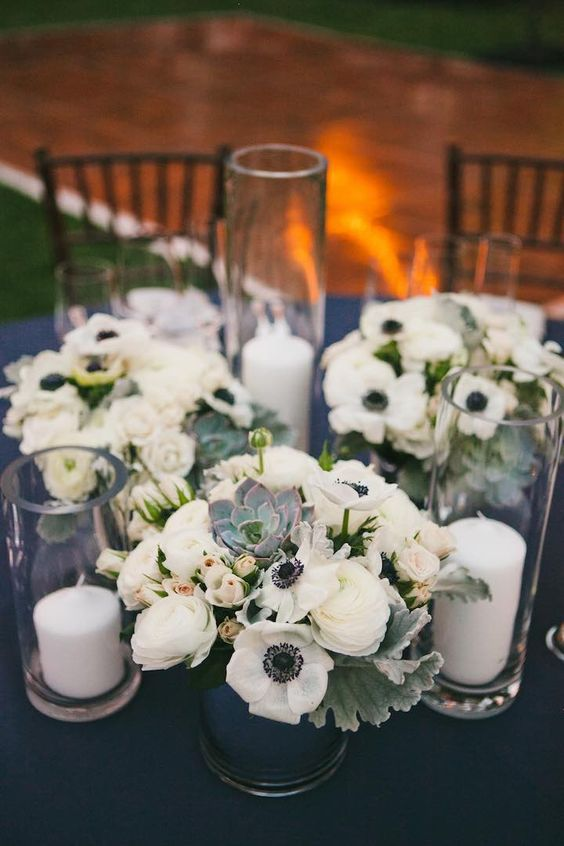 a chic anemone, ranunculus and pale greenery wedding centerpiece with succulents and tall candles in glasses is very cool and up-to-date