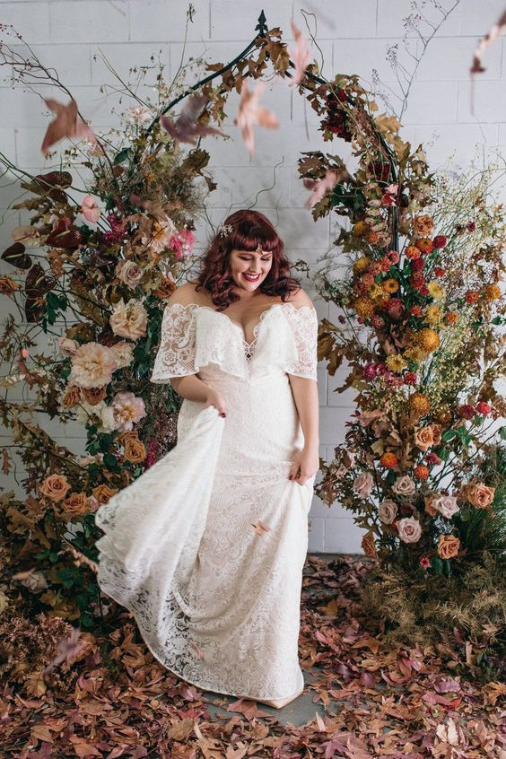 a chic fall garden wedding arch of a whimsy shape, with lots of bright fall blooms, greener and fall leaves plus leaves on the floor