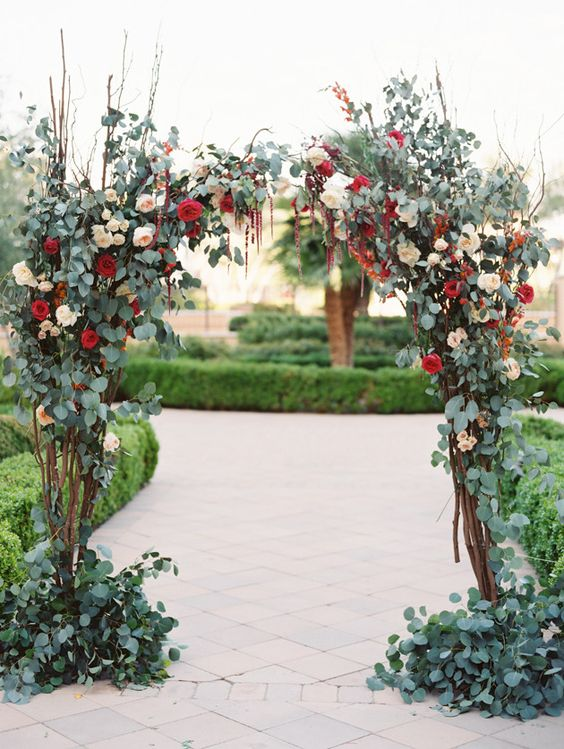 a chic fall wedding arch covered with greenery, blush and red blooms plus some twigs for a more eye-catchy looks is a very cool idea for an autumen garden wedding